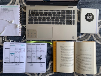 Computer, planner, notes, and book sitting on a table