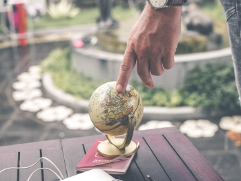 Person touching a small globe that is sitting on a park bench