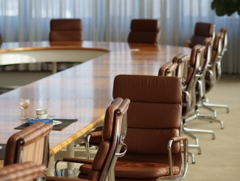 Board room style table with chairs around it, one turned toward the camera