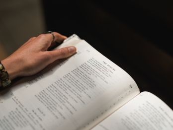 A person holding a Bible open to the Psalms
