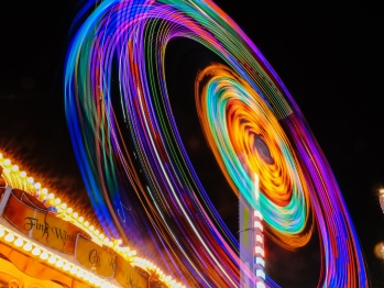 Time lapse of a ferris wheel at night creating circles of neon colors