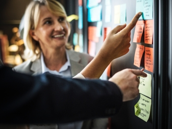 Group of people pointing at post-it notes on a board
