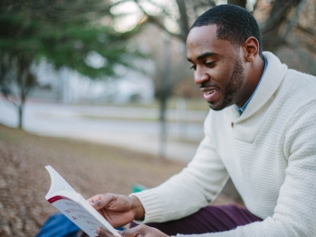 Black man wearing a white sweater sitting outside reading a book